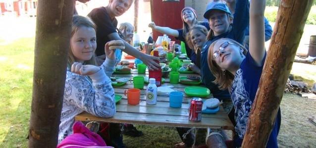 Upptäckarscouter äter hamburgare i sitt scoutkök på scoutläger